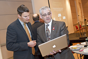 Dr. Julio Montaner (right) demonstrates the impact of expanded HIV treatment to Mayor Gregor Robertson.